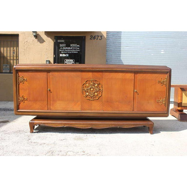Long French Art Deco palisander buffet by Jean Desnos. Elaborate bronze center medallion and hardware. . The sideboard are...