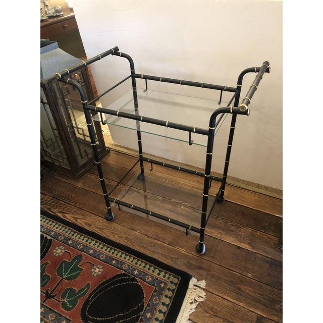 Hollywood Regency metal two tier bar cart having black and gold faux bamboo handles and frame and two glass shelves on...