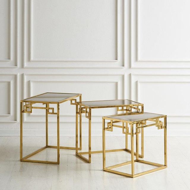 Set of three brass nesting tables with Greek key design and mirrored glass tops in an original rose gold tone. Italy,...