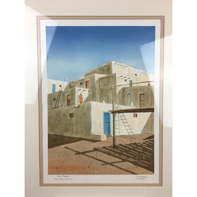 Beautiful framed watercolor art by Alexander Daube. Depicted in this watercolor is Taos Pueblo in New Mexico. A multistory...