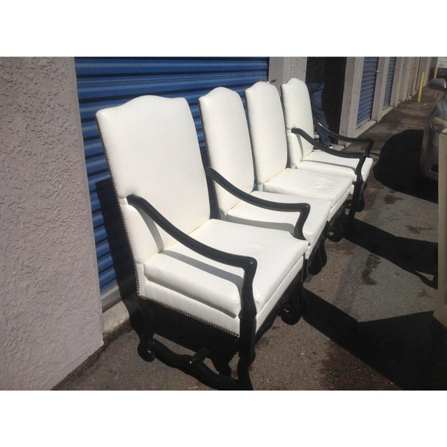 Set of 6 Tuscan style dining chairs. Done in a off white faux leather with nail head trim . The finish is a matte black....