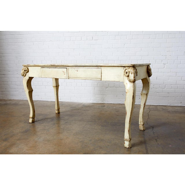 Gorgeous Italian lacquered writing table or desk featuring hand carved neoclassical ram's head motifs on each corner. The...