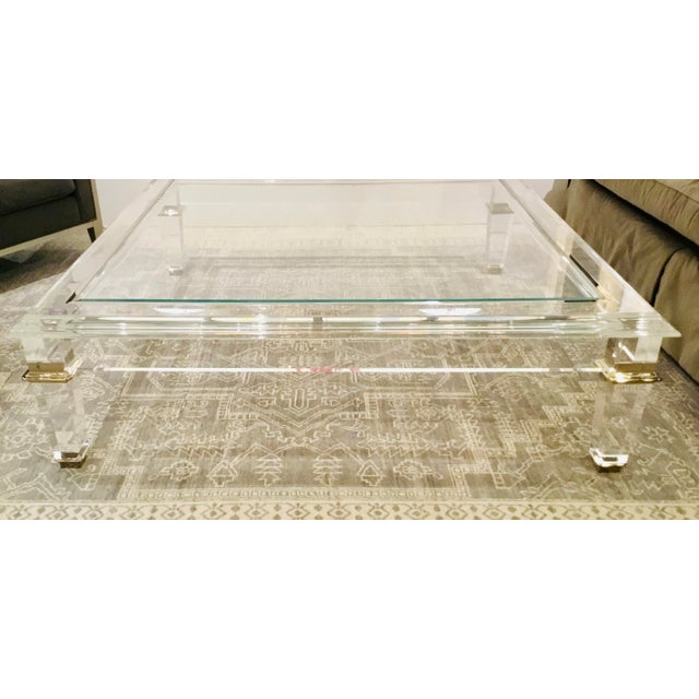Original retail $8600, stylish Caracole Signature contemporary acrylic Pierre cocktail table, warm brass accents, glass...