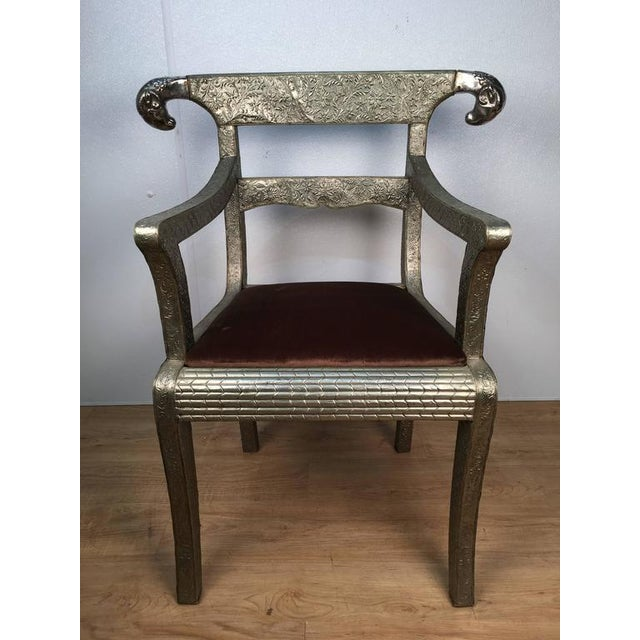 Offered is an Anglo-Indian ram's head armchair, clad in silver metal with cast heads and upholstered seat.