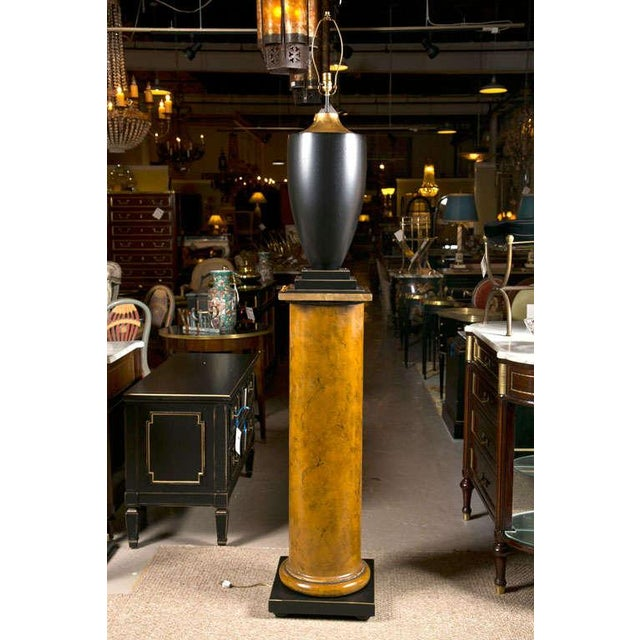 Pair of lamps on columns. Possibly 3rd quarter of 20th century. Lamps are ebonized with triple squared base and attached...