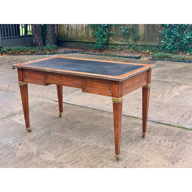 Beautiful vintage mid century Directoire style writing desk with leather top and brass trim. The desk has three drawers...