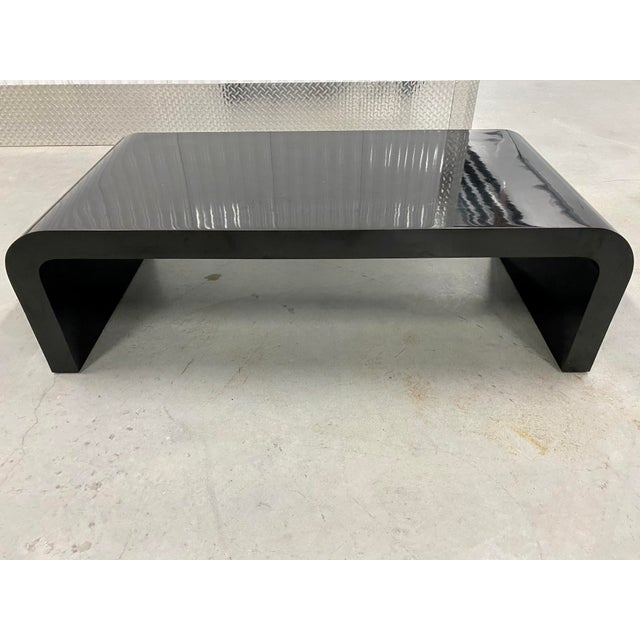 Fabulous sculptural waterfall high gloss black coffee table inspired by Karl Springer. Features bentwood wood frame...