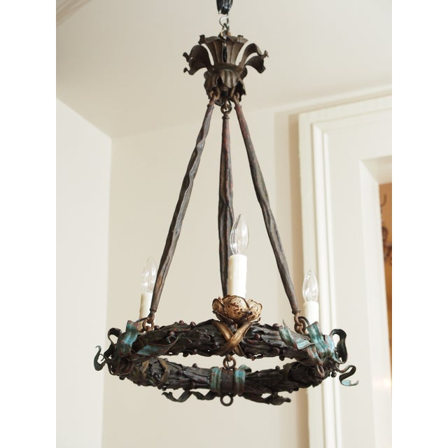 A painted iron chandelier in the form of wreath suspended by fabric and joined by a foliate crown. The detailed wreath is...