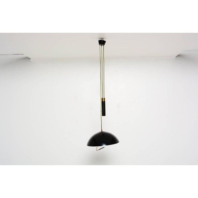 For your consideration a unique hanging light by Stilux Milano. Overside spun aluminum shade in black satin finish. Brass...