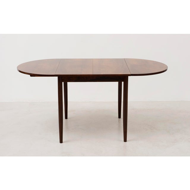 Elegant drop leaf dining table in rosewood designed by Niels Moller. Drop leaves can be removed and two extra leaves exist...