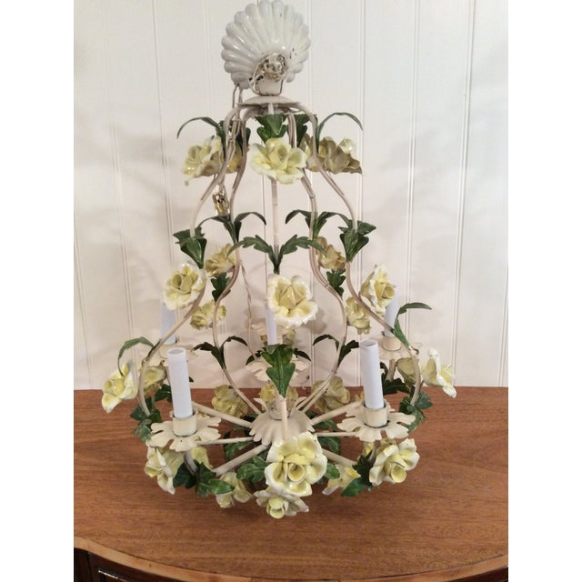 This is a beautiful Italian Tole chandelier with 6 candles and 32 porcelian roses. I bought it used for my home 20 years...