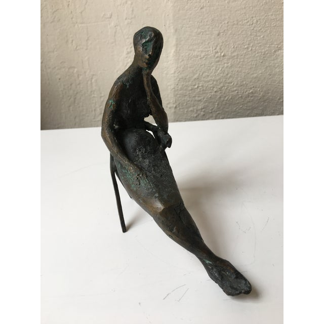 Small Bronze Seated Lady by Laura Ziegler 1956. Lady sitting in a chair with crossed legs, head in hand.