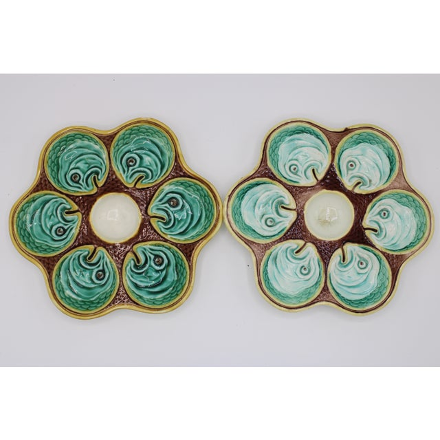 A superb pair of antique English Majolica oyster plates. There are six wells for oysters per plate and a central well for...