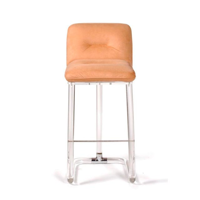 A set five bar stools with upholstered back and seat that swivel resting on Lucite bases in a tripod style form where the...