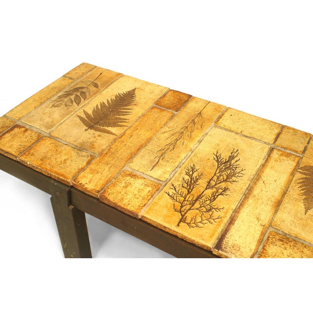 French 1960s rectangular coffee table with a brown painted wood frame on four legs and supporting a ceramic tile top...