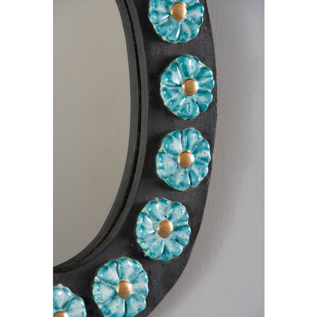 Circa 1970s oval mirror has a black ceramic frame adorned with porcelain blue flowers with gold centers.