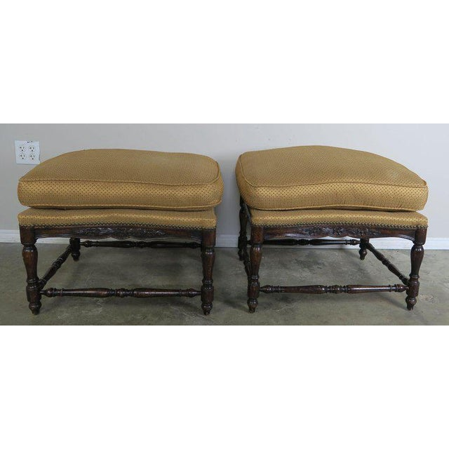 Pair of French Provincial style walnut benches that are upholstered in a high end golden colored designer silk with gold...