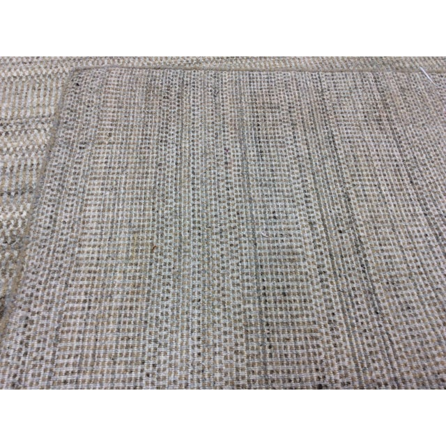 "A modern updating of a traditional ""Grass"" style. This handmade 100% Indian wool rug in beige and silver will harmonize..."