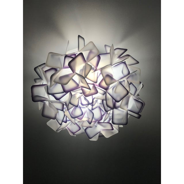 Exquisite ceiling light or wall sconce comprised of multifaceted interlocking resin squares. The square clusters are made...
