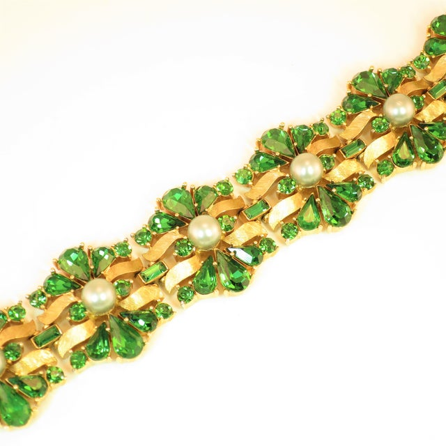 Offered here is a Crown Trifari Alfred Philippe-designed heavily-gilded rhodium bracelet embellished with emErald...