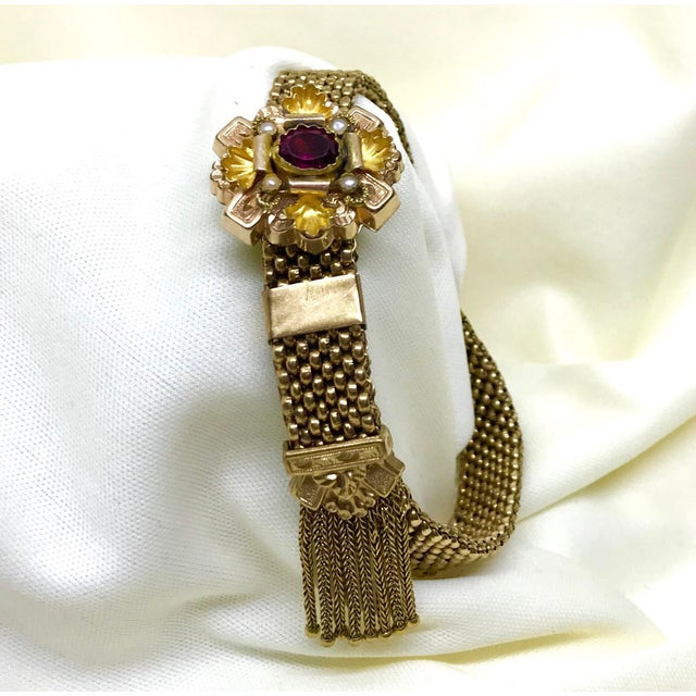 Antique Victorian garnet and pearl gold filled mesh bracelet with a foxtail chain tassel. The ornately designed top piece...