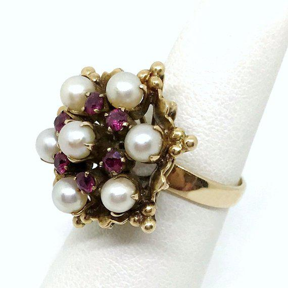 18K gold cocktail ring set with seven 4mm cultured pearls and embellished with six rubies. This Circa 1960s cocktail ring...