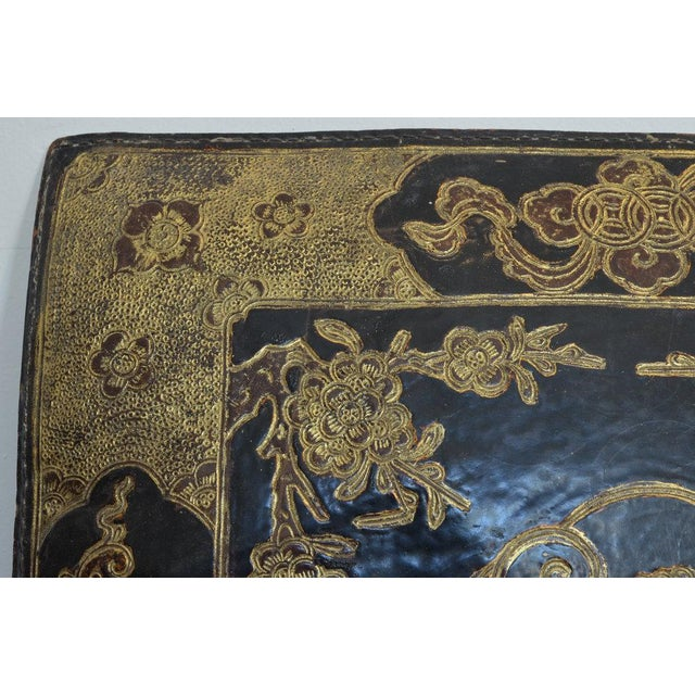 Antique Embossed Leather Chinese Cushions. embossed leather - one black, one red. one has original stuffing, one is empty....