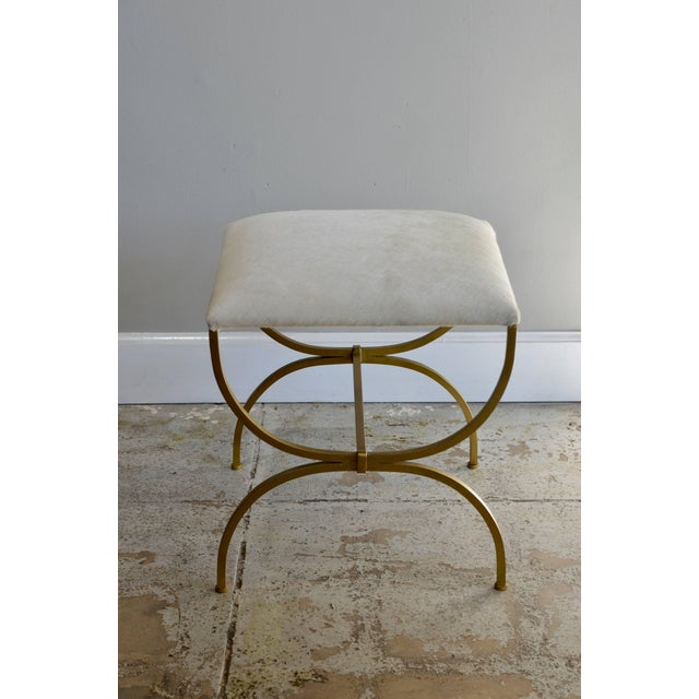 The 'Strapontin' gilt metal and white hide stool by Design Frères.