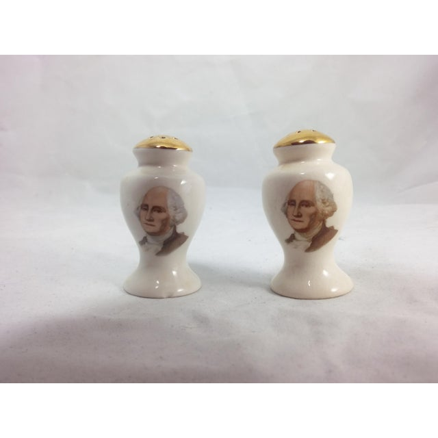 Set of George Washington ceramic salt and pepper shapers with gold detail. Some wear to the gold detail. A tiny chip at...