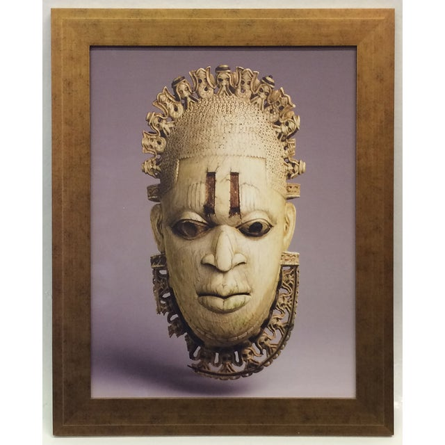 This photograph of an African mask is printed on canvas and framed in a gilded gold frame. This African mask is carved out...