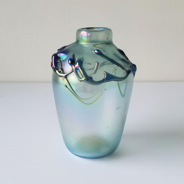 A beautiful small glass-blown vase by Peter Vizzusi in 1977. When light shines on the iridescent glass, new colors are...