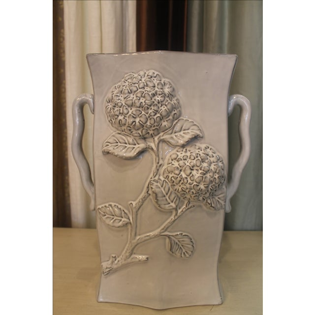 This lovely gray ceramic vase features a raised hydrangea design. It has two handles on the side for easy handling. The...