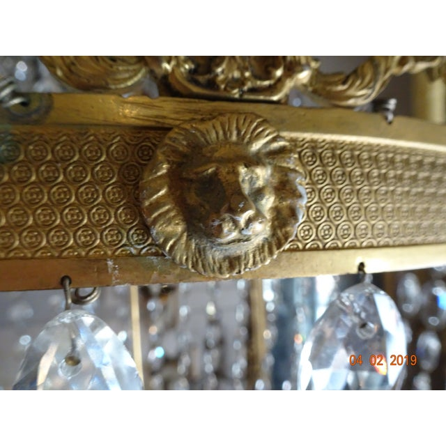 Stunning crystal chandelier on ormolu brass frame with 6 lights. Leaf crown with crystal pendants. Each arm has an...