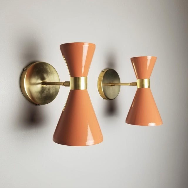 """The """"Campana"""" wall sconce or reading light shown in unlacquered brass and dark blush enamel fabricated in NYC by Blueprint..."""