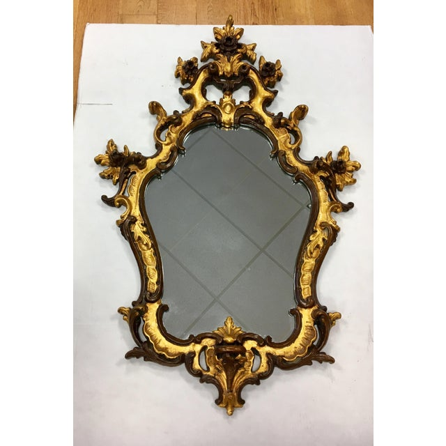 Beautifully hand carved Italian Rococo style giltwood shield wall mirror with elegant design features that include scrolls...