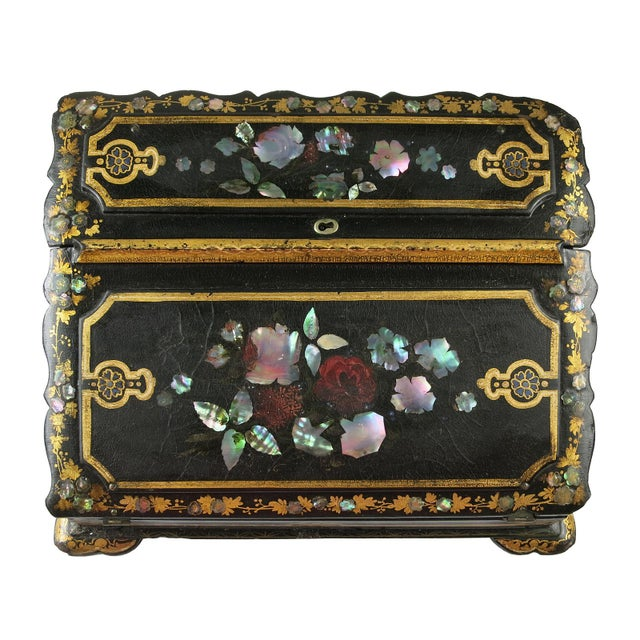 A Victorian mid nineteenth century papier mâché lap desk. The slanted lid with floral decoration is gilded, painted and...