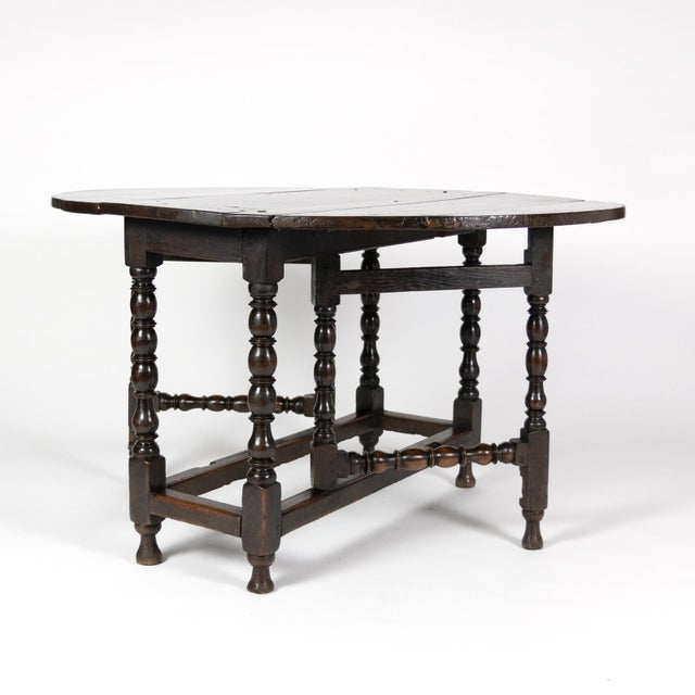A handsome & richly patinaed English Oak Gateleg Table with bobbin turned legs, circa 1800. The oval top above gate leg...