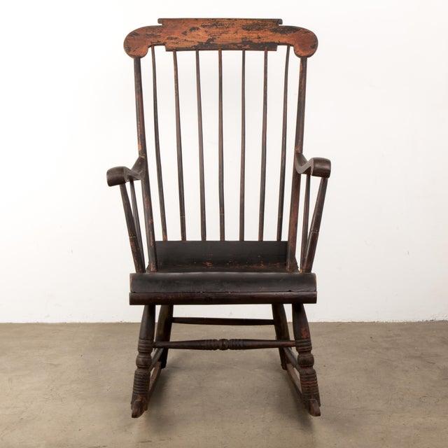 An early 19th century ebonized American Windsor rocking chair with remaining remnants of original painted designs with a...