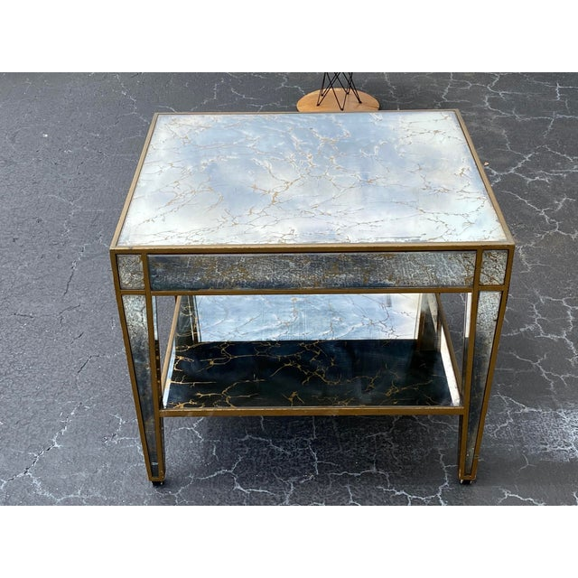 Hollywood Regency mirrored end table. Heavy and sturdy structure . Has wear on gold painted wood parts . No chips on the...