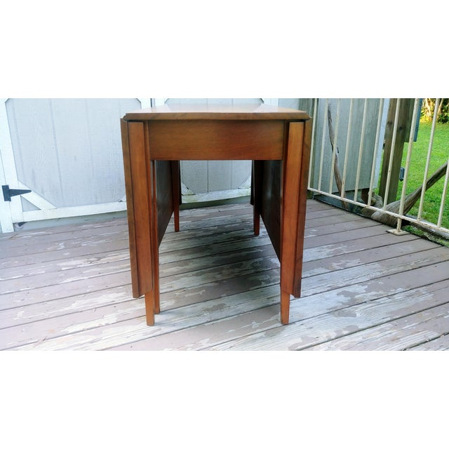 Item offered is a nice vintage solid Pecan wood Shaker style drop leaf dining table. It has a nice thin line Mid Century...