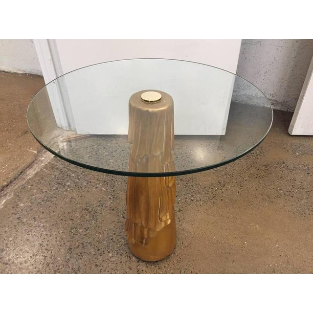 Decorative side table with a painted gold wood base. Has a round glass top with a central brass connector.