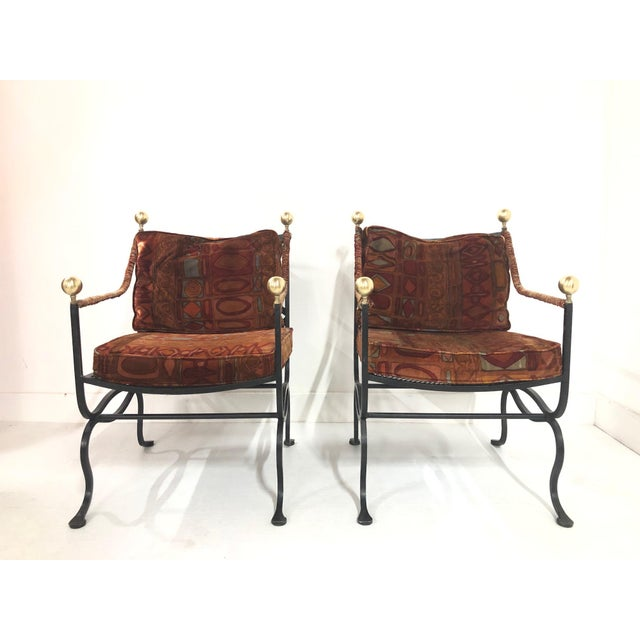 Pair of Italian Hollywood Regency Savonarola Chairs. Chairs have wrought iron frames with brass round finials to the back...
