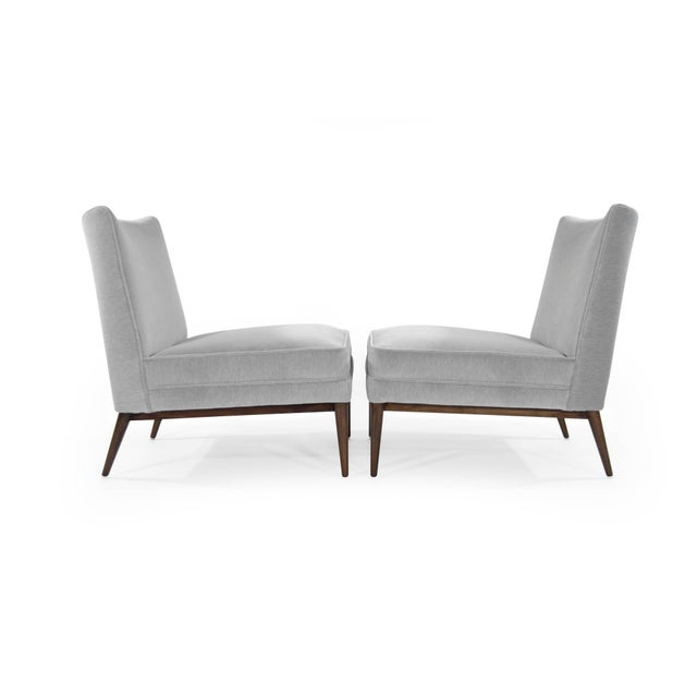 Pair of slipper chairs by Paul McCobb for Directional, circa 1950s. Newly upholstered in grey mohair, walnut bases fully...
