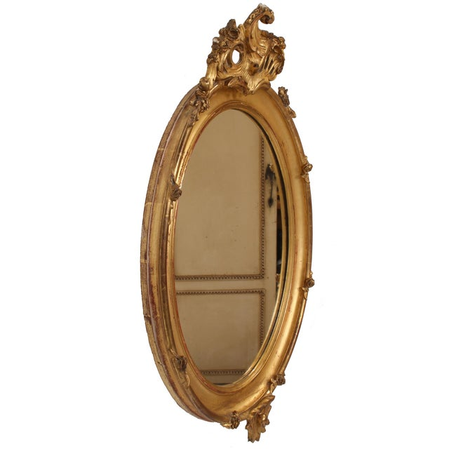 Romantic French Louis XV style oval giltwood mirror with an intricate foliate-and-scroll crest, delicate carved roses...