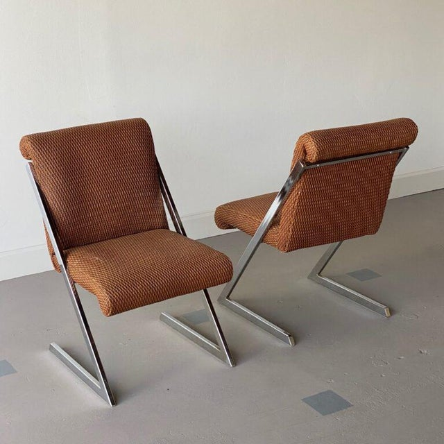 Pair of cantilever metal chairs with synthetic rattan upholstery. Height: 33.5″ Width: 21″ Depth: 27″ Seat Height: 17.5″