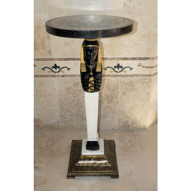 A lovely little statement piece in this table. Pedestal table with a marble support decorated with an Egyptian figure....