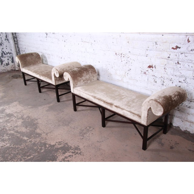 An exceptional pair of mahogany and velvet upholstered benches by Baker Furniture. The benches feature solid dark mahogany...