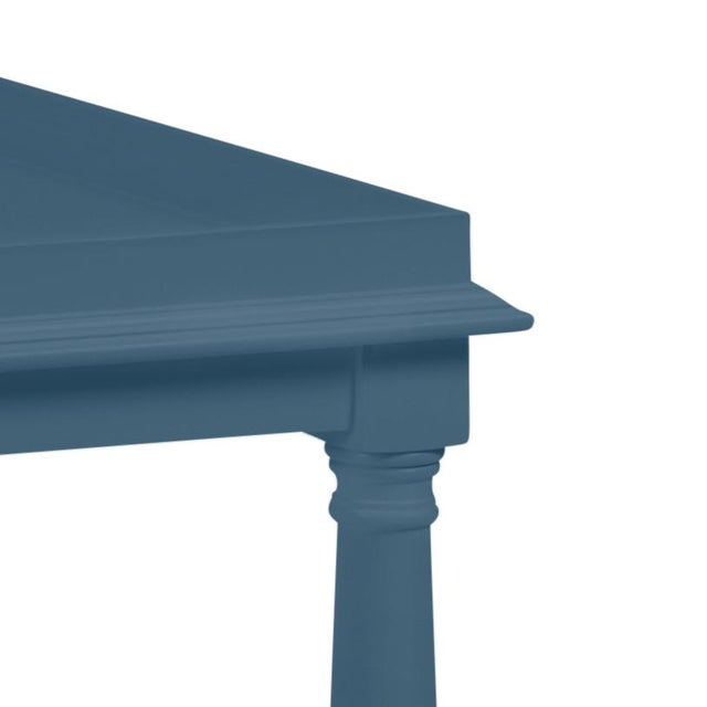 Made of acacia wood, this cocktail table features a gallery shelf and turned legs. Color is Benjamin Moore Van Deusen Blue...