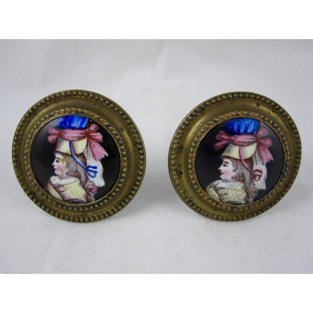 An amazing pair of enameled curtain tiebacks or mirror supports showing the polychrome image of a woman in profile wearing...