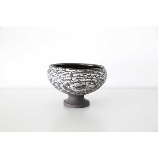 A beautiful vase in urn shape from Paris. The glaze is black matte on the exterior with white textured speckles, black...